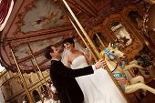 pic of amusement  - Bride and groom on carousel in amusement park - JPG