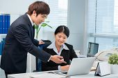 image of korean  - Korean manager and his female colleague working on laptop - JPG