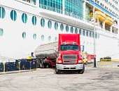 stock photo of fuel tanker  - A truck pumping fuel into a luxury cruise ship - JPG
