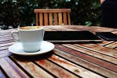 picture of coffee coffee plant  - Shot of a digital tablet smart phone and coffee mug on a wooden table with empty chair black touch screen computer on cafe table with coffee cup - JPG