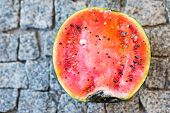 picture of rotten  - Rotten watermelon on a grey stone background - JPG