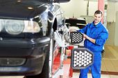 picture of suspension  - car mechanic installing sensor during suspension adjustment and automobile wheel alignment work at repair service station - JPG