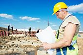 picture of millwright  - construction builder worker with blueprint project at building site  - JPG