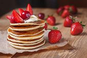 image of breakfast  - Homemade pancakes delicious breakfast or lunch dessert with strawberry, honey and butter on rustic kitchen table. Natural light rustic style.