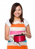picture of saucepan  - Asian housewife using saucepan with oven glove - JPG