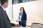pic of receptionist  - Businessman talking with receptionist in office - JPG