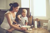 stock photo of real  - Mom with her 2 years old child cooking holiday pie in the kitchen to Mothers day - JPG