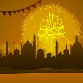 stock photo of arabic calligraphy  - Shiny arabic calligraphy text of Eid Mubarak with silhouette of islamic mosque for muslim community festival celebration - JPG