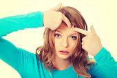 stock photo of forehead  - Teenage woman checking wrinkles on forehead  - JPG