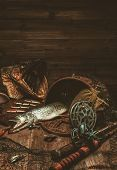 stock photo of fishing bobber  - Fishing tools and fresh pike on a wooden table - JPG