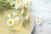 pic of chamomile  - Glass of cold chamomile tea with ice cubes and chamomile flowers on color wooden background - JPG