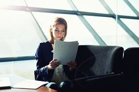 image of half  - Half length portrait of female managing director examining paperwork in bight light office interior attractive business woman read some documents before meeting soft focus filtered image - JPG