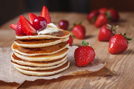 picture of breakfast  - Homemade pancakes delicious breakfast or lunch dessert with strawberry, honey and butter on rustic kitchen table. Natural light rustic style. ** Note: Shallow depth of field - JPG