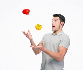 picture of juggling  - Young man juggling pepper isolated on a white background - JPG