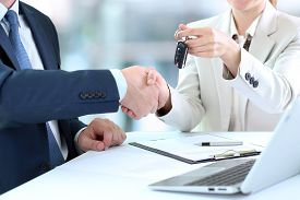 image of handshake  - Car saleswoman handing over the keys for a new car to a young businessman  - JPG