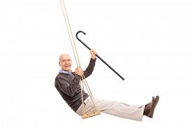 pic of swing  - Studio shot of a joyful senior swinging on a swing and holding a cane isolated on white background - JPG