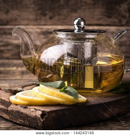 Hot Tea In Glass Teapot And Cup With Spoon And Steam On Wooden Table