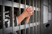 Prisoner behind bars with hands clenched outside bars poster
