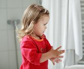 Small Girl Washing Her Hands poster
