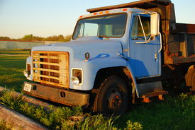 stock photo of dump_truck  - Old blue dump truck on the side of the road - JPG