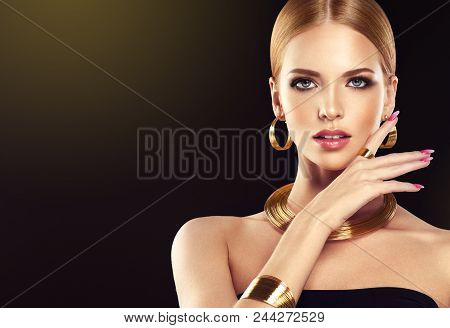 54f88606e1f Beautiful girl with golden set jewelry . Woman in a necklace with a ring,  earrings and a bracelet. Beauty and accessories. Black background poster.