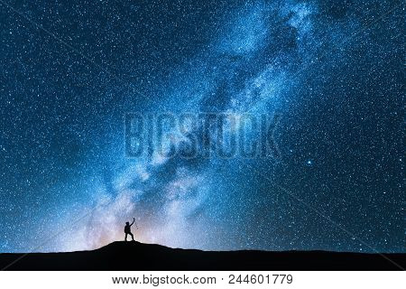 poster of Silhouette Of Man With Trekking Poles Against Amazing Milky Way At Night. Space Background. Landscap