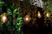 Design Of Yellow Vintage Bulbs And Tropical Green Leaves. Retro Beautiful Lamp Lights On Garland Wit poster