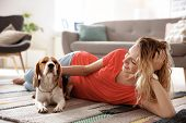 Young Woman With Her Dog At Home poster