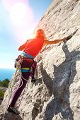Rock Climber On A Rock. Girl Climbs The Rock On The Background Of A Beautiful Mountain Landscape And poster
