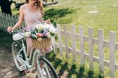 Partial View Of Woman In Stylish Dress With Retro Bicycle With Wicker Basket Full Of Flowers At Coun poster