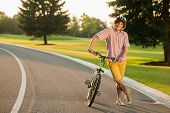 Smiling Man Resting With Bicycle On Country Road. Happy Young Man In Casual Wear Having Rest With Bi poster