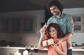 Portrait Of Happy Married Couple Celebrating Anniversary In Kitchen. Husband Is Holding A Gift Box I poster