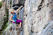 A Woman Climbs The Rock. Training On Natural Terrain. Extreme Sport. The Climber Trains On A Natural poster