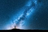 Silhouette Of Man With Trekking Poles Against Amazing Milky Way At Night. Space Background. Landscap poster