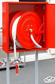 stock photo of firehose  - High pressure fire hose at red spool - JPG