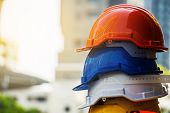 Orange, Blue, White And Yellow Hard Safety Helmet Hat. Engineer, Construction And Safety Concept. Co poster