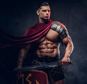 Brutal Ancient Greece Warrior With A Muscular Body In Battle Uniforms Posing On A Dark Background. poster