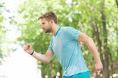 Moving To His Goal. Man Confident Young Running In Park, Side View. Sportsman Ambitiously Moves To A poster