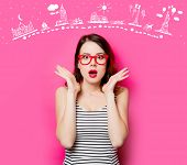 Portrait Of Beautiful Surprised Young Woman In Glasses On The Wonderful Pink Studio Background And T poster