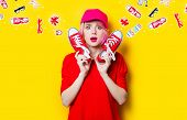 Portrait Of Beautiful Surprised Young Woman With Red Gumshoes On The Wonderful Yellow Studio Backgro poster