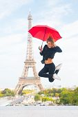 Happy Girl Travel In Paris, France. Woman Jump With Fashion Umbrella. Parisian Isolated On White Bac poster