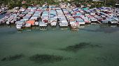 Aerial photo poor water village in Asia. Climate change threatens these coastal slums. Poverty poster