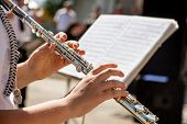 Girl Plays On Flute. Flute In  Hands Of  Girl During The Concert. Professional Musician Playing On   poster