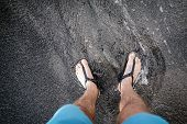 Life Balance Concept. Man Looking Down At Feet And Sandals On Volcanic Black Sand Beach. Legs Relaxi poster