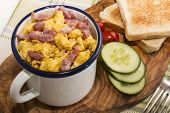 Scrambled Eggs With Roasted Bacon In An Enamel Mug, Served With Toasted Slice Of Bread, Cucumber Sli poster