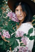 Stylish Boho Woman In Hat Posing At Lilac Flowers In Sunny Spring Park. Calm Portrait Of Beautiful H poster
