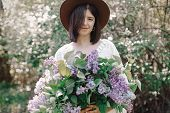 Stylish Boho Woman In Hat Holding Lilac Flowers Bouquet In Sunny Spring Park. Calm Portrait Of Beaut poster