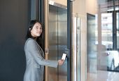 Door Access Control - Young Officer Woman Holding A Key Card To Lock And Unlock Door For Access Entr poster