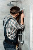 Installer Standing In Bathroom And Installing Pipe Near Shower Head poster