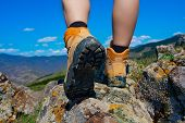 stock photo of boot  - Hiking boot on the rocks in mountain - JPG
